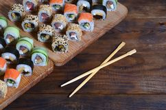 A detailed shot of a set of Japanese sushi rolls and a device for their use chopsticks, which are located on a wooden cutting boa. Rd on a table in the kitchen Royalty Free Stock Photo