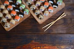 A detailed shot of a set of Japanese sushi rolls and a device for their use chopsticks, which are located on a wooden cutting boa. Rd on a table in the kitchen Stock Image