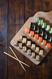 A detailed shot of a set of Japanese sushi rolls and a device for their use chopsticks, which are located on a wooden cutting b. Oard on a table in the kitchen Stock Photography