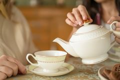 Hands of young woman with white china teapot pouring tea into cup of her senior mother. Detailed Shot Of The White Porcelain Teacup And Cup Of Tea Being On The royalty free stock images