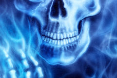 Detailed skull and skeleton hand and blue fire, on black background. Stock Photo