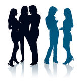 Silhouettes of young women chatting with each othe Stock Photo