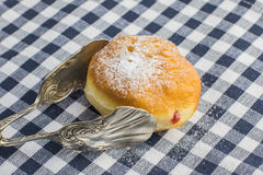 Detailed view on Berliner (doughnut) with strawberry jam Stock Photo