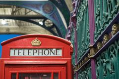 Detailed view of the colourful wrought ironwork and red telephone box at Smithfield meat market, London UK. Detailed view of the colourful wrought ironwork and royalty free stock images