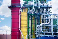 Detailed view of factory plant on sky background. Detailed close up view of factory plant with colorful tower and metallic tubes on sky background Stock Photos