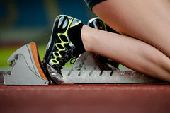 Detailed view of a female sprinter. In starting blocks on a running track Stock Photography