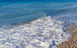 Detailed view of gentle waves lapping against a pebbly beach in Greece Rhodes. royalty free stock photo