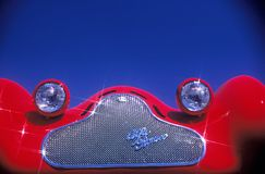 A detailed view of a highly polished chrome grill and bug eyed headlights on a red vintage Alpha Romeo sports car. Stock Images