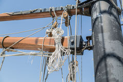 detailed view of old tall ship parts and ropes against blue sky background Stock Image