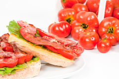 Detailed View of Plated BLT with Field Tomatoes. A studio close up of an open-faced BLT with freshly washed field tomatoes in the background with sharp focus on Stock Image