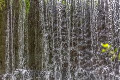 Detailed view of a small cascade on river, colorful and texture of water falling stock photo