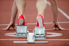 Detailed view of a sprinter. Wearing sprinting shoes with spikes, leaving starting blocks. Selective focus Royalty Free Stock Photos
