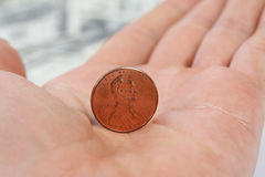 Detailed view standing penny on male hand Royalty Free Stock Photos