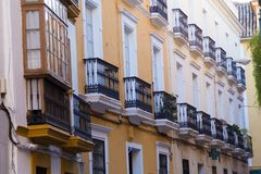 Building and street in Seville, Spain, details of old facade, wall with wooden frame windows. stock images