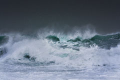 Detailed winter storm wave breaking and splashing on shore Stock Photography