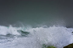 Detailed winter storm wave breaking and splashing on shore Stock Photo