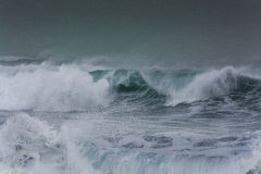 Detailed winter storm wave breaking and splashing on shore Royalty Free Stock Photography