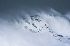 Detailed winter storm wave breaking and splashing on shore Stock Images