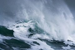Detailed winter storm wave breaking and splashing on shore Royalty Free Stock Images
