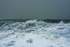 Detailed winter storm wave breaking and splashing on shore Stock Photos