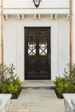 Detailed wooden front door of white brick home Stock Photo