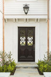 Detailed wooden front door of white brick home. Intricate design on a wooden front door to a family home. Door features criss-cross glass patterns. House is Royalty Free Stock Photo