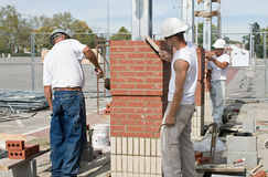 Detailing the Brickwork. Construction bricklayers using hand tools to detail or finish the brickwork Stock Image