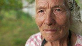 Detailportret van een zeer oude vrouw met een hoofddoek op haar hoofd die in haar tuin werken De camera trekt weg en kan zijn stock footage