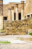 Columns Beyond Stone Wall in Pompeii. Details of the Ancient city of Pompeii destroyed by volcano of Vesuvius royalty free stock photography