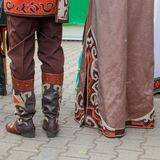 Details of the Bashkir traditional national clothing. Men`s leather boots with applications and the bottom of women`s dresses wi stock images