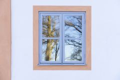 Details of beautiful blue window and white house wall. Nice reflections of trees in the glass stock photography