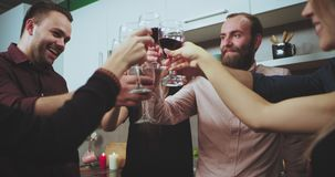 Details of a big group of a young guys and ladies cheers with wine glasses in front of the camera at the party. 4k stock video