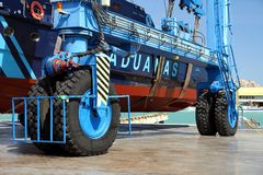 Details of big tires on shipyard travelift carrying a boat. Great tires used in a shipyard of Alicante city for carry a coastguard for made reparations royalty free stock photography