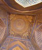 Blue interior of dome with gold gild of Tile Karl Madrasa in The. Details of blue carved and painted interior ceiling with gold gild of the Tile Karl Madrasa in royalty free stock image