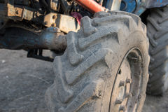 Details of a blue village tractor with dirty wheels, engine, rud Royalty Free Stock Photos