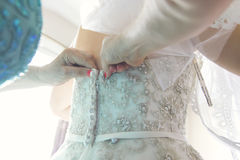 Details of a bridge dressing in ornate wedding dress. A bridge being helped into her ivory wedding dress from behind. A woman fastening the corset of a detailed Royalty Free Stock Images