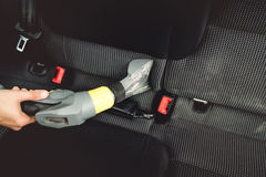 Details of car worker, vacuuming upholstery seats with steam cleaner Royalty Free Stock Image