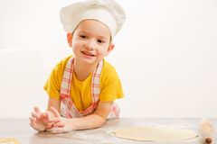 Details of children`s hands kneading dough. Cheerful cook child boy in a cap prepares burritos Royalty Free Stock Photos