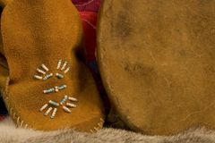 Details of a Childs Moccasin. A child's moccasin sits next to a hand drum. Textures are visible at 100 royalty free stock photos