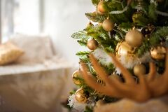 Details of Christmas tree decor in gold close-up and copy space. Christmas tree branches and yellow toys with empty space. New Yea