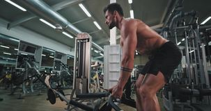 Details closeup of a attractive young man doing a workout in a gym class concentrated and very tired working hard stock video