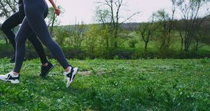 Details closeup at nature two running ladies take video of legs while running through the green grass beside of the stock footage