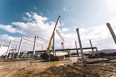Details of construction site with crane lifting prefabricated concrete framework, unloading and cargo details stock images