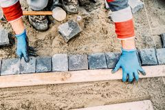 details of construction worker laying granite cobblestone on road pavement stock photos