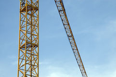Details of a crane. Orange painted construction crane in front of blue sky Stock Photos