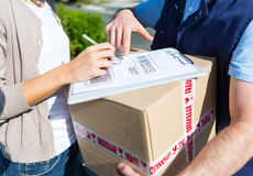 Details of a customer signing delivery note Stock Photos