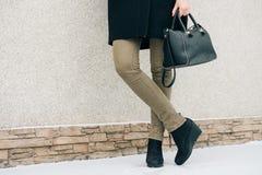 Details der Kleidungs der Frauen: Weibliche Beine in den grünen Jeans und im blac stockfotografie