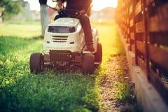 Details der Landschaftsgestaltung und der Gartenarbeit Arbeitskraft, die industriellen Rasenmäher reitet Stockbild