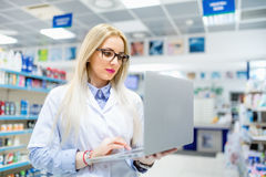 Details des Apothekendrugstores - sexy blonder Apotheker, der nach Antibiotika auf Laptop sucht Stockfotografie