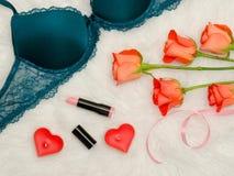 Details des Smaragdmieders mit Spitze Orange Rosen, Lippenstift, Kerzen in Form des Herzens modernes Konzept Stockbild
